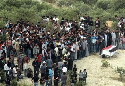 Syrian people attend a funeral in a rural area on the Syrian side of the border zone between Turkey and Syria near the Turkish village of Guvecci, 50 kilometres (31 miles) from Hatay city centre, June 11, 2011. REUTERS/Stringer
