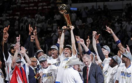 Dallas Mavericks' Dirk Nowitzki lifts the Larry O'Brien Championship Trophy with his teammates after they beat the Miami Heat in Game 6 to win the NBA Finals basketball series in Miami, June 12, 2011. REUTERS/Hans Deryk