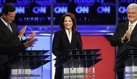 Republican presidential hopefuls (L) former U.S. Senator Rick Santorum (R-PA) and (R) former Speaker of the U.S. House of Representatives Newt Gingrich (R-GA) applaud U.S. Rep. Michelle Bachmann (R-MN) as she is introduced at the first New Hampshire debate of the 2012 campaign in Manchester, New Hampshire June 13, 2011. REUTERS/Shannon Stapleton