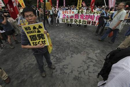 Protesters attend an anti-nuclear rally during a memorial for the third month anniversary of the March 11 earthquake and tsunami, in Tokyo June 11, 2011. The banner reads, ''Stop all nuclear power plants'' and the poster on left reads ''Get rid of nuclear power plants''. REUTERS/Kim Kyung-Hoon