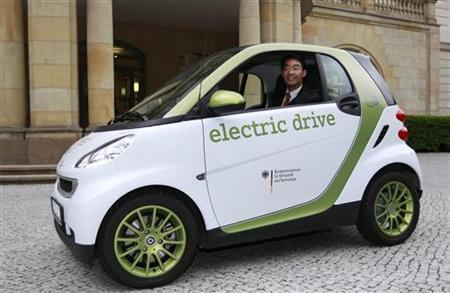 Economy Minister Philipp Roesler poses in a electric car after taking over the economy ministry from his predecessor in Berlin May 16, 2011. REUTERS/Thomas Peter