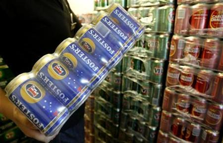 A customer carries Fosters beer cans from the cool room at a liquor store in Melbourne November 6, 2008. REUTERS/Mick Tsikas
