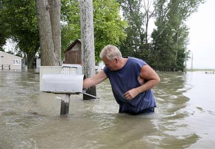 Marty Stouffer checks the content of a mailbox while walking through floodwaters to his parents' home in Cottonwood Marina, north of Omaha June 14, 2011. REUTERS/Lane Hickenbottom