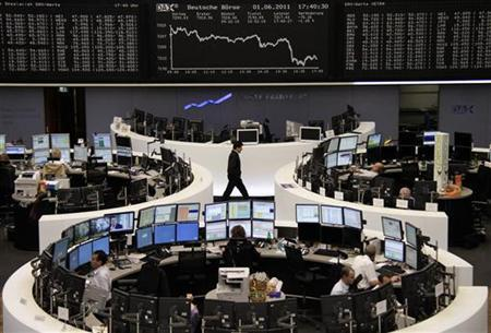 Traders are pictured at their desks in front of the DAX board at the Frankfurt stock exchange June 1, 2011. REUTERS/Remote/Amanda Andersen
