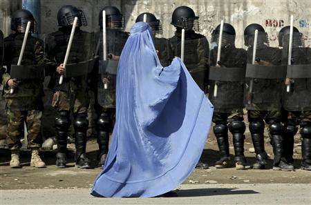 A woman walks past riot police outside a gathering in Kabul's stadium in this February 23, 2007 file photo. REUTERS/Ahmad Masood/Files