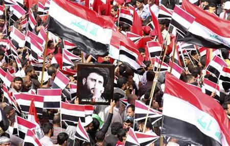 A demonstrator holds a picture of Shi'ite cleric Moqtada al-Sadr during a protest in Baghdad April 9, 2011. REUTERS/Kareem Raheem