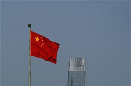 A Chinese national flag flies outside the Xinhua Gate of the Zhongnanhai leadership compound, the residence of China's top leaders, with World Trade Centre Tower III, a 330-meter-tall skyscraper, the tallest in Beijing in the background November 11, 2010. REUTERS/Petar Kujundzic