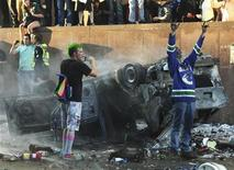 <p>Vancouver Canucks fans scream and take photos of an overturned burnt pickup truck during riots in downtown Vancouver, British Columbia after the Canucks lost Game 7 of the NHL Stanley Cup playoffs to the Boston Bruins June 15, 2011. REUTERS/Anthony Bolante</p>