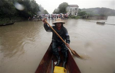 A man paddles a boat through a flooded area in Banshan Cun, Zhejiang province June 17, 2011. REUTERS/Carlos Barria