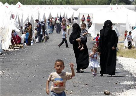 Syrian refugees walk along a refugee camp in the Turkish border town of Boynuegin in Hatay province June 18, 2011. REUTERS/Umit Bektas