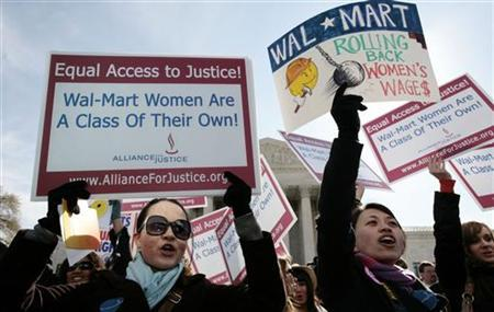 Women protesters hold signs in front of the Supreme Court while class action lawsuit Dukes v. Wal-Mart is being argued inside the court in Washington, March 29, 2011. REUTERS/Larry Downing
