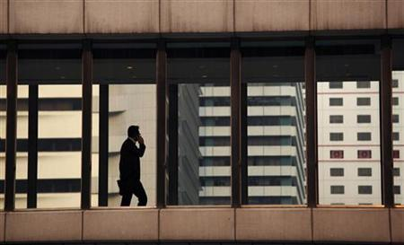A man talks on a mobile phone while crossing a foot bridge at Hong Kong's financial Central district June 1, 2011. REUTERS/Bobby Yip