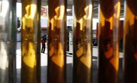 An employee of a petrol station is seen between samples of engine oil at a gas station in Tokyo February 25, 2011. REUTERS/Toru Hanai
