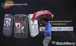 <p>A man tries to hold on to his umbrella as he walks past a Blackberry advertisement billboard in Mumbai August 30, 2010. REUTERS/Danish Siddiqui</p>