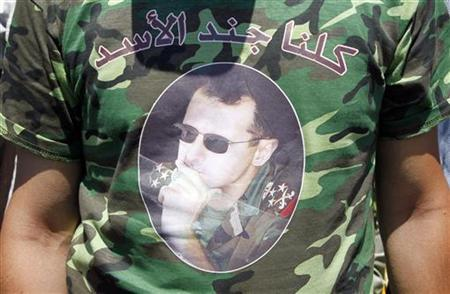 A supporter wears a T-shirt with a picture of Syrian President Bashar al-Assad in al-Umawiin square in Damascus June 21, 2011, as several large government rallies take place across the country to support him. REUTERS/Khaled al-Hariri