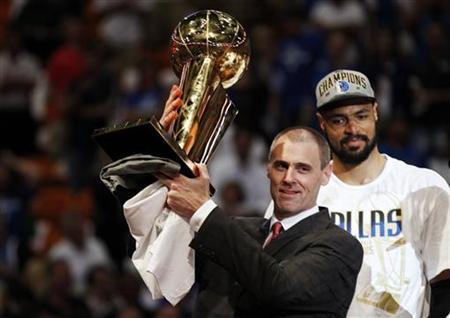 Dallas Mavericks head coach Rick Carlisle (L) holds the Larry O'Brien Championship Trophy in front of Mavericks center Tyson Chandler after the Mavericks beat the Miami Heat in Game 6 to win the NBA Finals basketball series in Miami, June 12, 2011. REUTERS/Hans Deryk