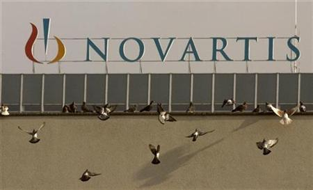 Pigeons sit on a roof in front of the logo of Swiss drugmaker Novartis at the company's plant in Basel January 28, 2009. REUTERS/Arnd Wiegmann