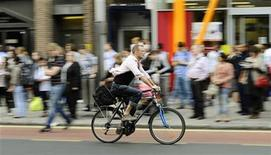 <p>A man cycles past commuters waiting at a bus stop outside Waterloo Station in London September 7, 2010. REUTERS/Dylan Martinez</p>