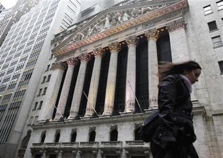A woman walks outside the New York Stock Exchange during a rain storm, March 10, 2011. REUTERS/Brendan McDermid