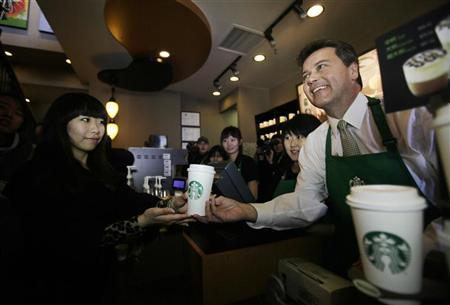Starbucks Coffee International President John Culver (R) poses for the media as he passes a cup of coffee in a container with the new Starbucks logo to the first customer after the official unveiling ceremony for its new logo at the Solana store in Beijing March 8, 2011. REUTERS/Jason Lee