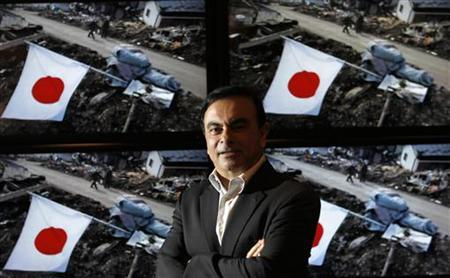 Carlos Ghosn, Chairman and CEO of Nissan and Renault, poses for a picture in front of television screens showing devastated areas caused by the March 11 tsunami and earthquake, taken by a Reuters photographer, before the Reuters Rebuilding Japan Summit in Tokyo June 22, 2011. REUTERS/Kim Kyung-Hoon