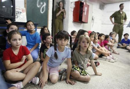 Israeli children sit inside a bomb shelter in a school in the central city of Givatayim June 22, 2011, as a siren is sounded during a nationwide drill which envisages heavy shelling and thousands of dead and wounded on several Israeli fronts. REUTERS/Nir Elias