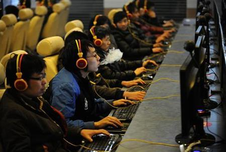 A man smokes while using a computer at an Internet cafe in Taiyuan, Shanxi province December 30, 2010. REUTERS/Stringer