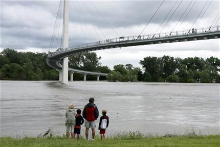 A family checks out the flooded Missouri River from beneath the Bob Kerrey Pedestrian Bridge in Omaha, Nebraska, June 21, 2011. REUTERS/Lane Hickenbottom