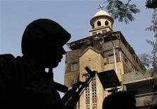 <p>A soldier stands guard near the Saint Mary church which was set on fire during clashes between Muslims and Christians on Saturday in the heavily populated area of Imbaba in Cairo May 8, 2011. REUTERS/Asmaa Waguih</p>