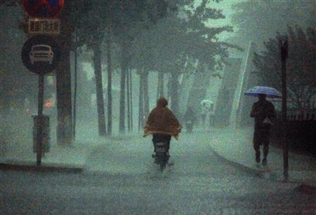 A man rides an electric bike as a pedestrian carries an umbrella during a heavy rain storm in Beijing June 23, 2011. REUTERS/David Gray