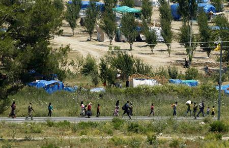 Syrian refugees walk as they enter the Turkish side of the border at the border zone between Syria and Turkey, near the Turkish village of Guvecci, 50 kilometres (31 miles) from Hatay province June 23, 2011. REUTERS/Umit Bektas