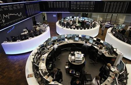 Traders are pictured at their desks in front of the DAX board at the Frankfurt stock exchange, February 15, 2011. REUTERS/Alex Domanski