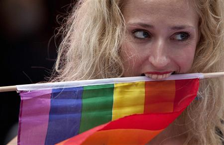 A protester clenches a rainbow flag with her teeth at a demonstration supporting same-sex marriages outside Sheraton Hotel where President Barack Obama was attending a function in New York June 23, 2011. REUTERS/Andrew Kelly