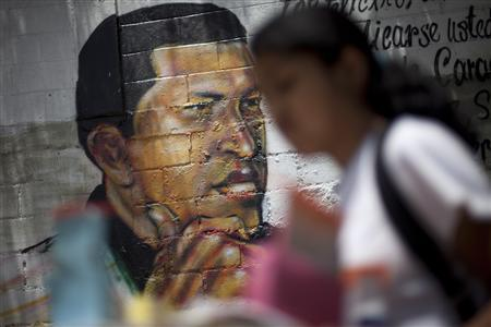 A girl walks past graffiti depicting Venezuelan President Hugo Chavez at the '23 de Enero' neighborhood in Caracas June 27, 2011. REUTERS/Carlos Garcia Rawlins