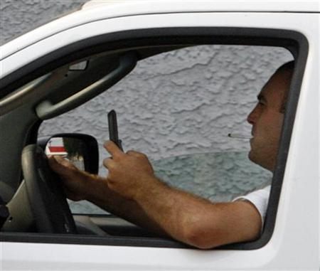 A man uses a cell phone while driving in Burbank, California June 25, 2008. REUTERS/Fred Prouser