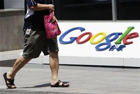 An employee walks past the logo of Google in front of its former headquarters, in Beijing June 2, 2011. REUTERS/Jason Lee