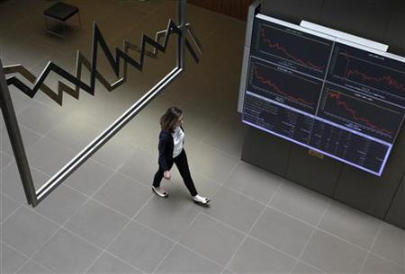 A woman walks past electronic boards displaying stock prices and economic index at the Athens stock exchange in Athens May 16, 2011. REUTERS/John Kolesidis )