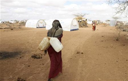 A Somali refugee carries jerry-cans of water from a tap at the Dagahaley camp in Dadaab, near the Kenya-Somalia border, April 3, 2011. Drought and two decades of violence have forced Somalis to flee their country and seek refuge at the three Dadaab camps. REUTERS/Natasha Elkington