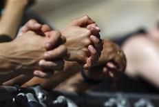<p>People pray during a religious service for bikers at the German Evangelical Church Congress in Dresden, June 4, 2011. REUTERS/Thomas Peter</p>