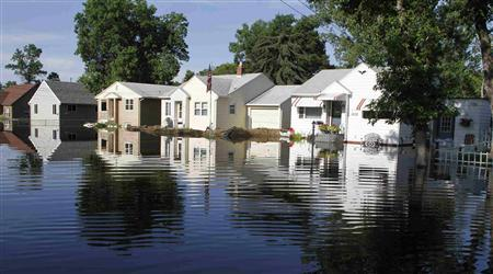 Homes seen in the morning light, are reflected in flood waters, with the earthen levee of one house (C) appearing to remain intact in Minot, North Dakota, June 25, 2011. REUTERS/Allen Fredrickson