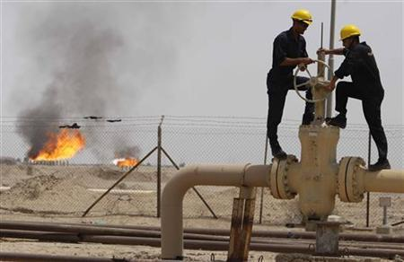 Workers adjust a valve of an oil pipe as smoke rises from burning excess gas (in the background) in Zubair oilfield in Basra, 420 km (260 miles) southeast of Baghdad May 23, 2011. REUTERS/Atef Hassan
