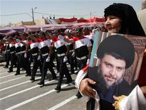 <p>A woman holds a picture of anti-U.S. Iraqi cleric Moqtada al-Sadr as his supporters march on a street in Baghdad's Sadr city May 26, 2011. REUTERS/Kareem Raheem</p>