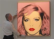 """<p>Foto de archivo. Empleado de Sotheby's con una obrea de Andy Warhol, """"Debbie Harry"""" en la casa de subastas de Sotheby's en Londres REUTERS/Luke MacGregor</p>"""