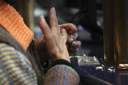 File photo of a woman taking off her ring at the desk of a certified appraiser at the Nacional Monte de Piedad (Mountain of Pity or Mountain of Mercy), the national pawnshop in downtown Mexico City January 12, 2011. REUTERS/Jorge Dan