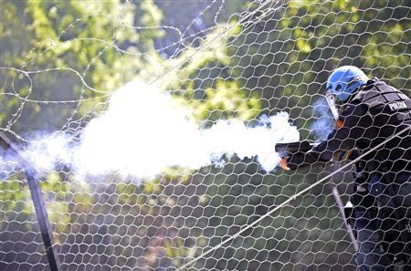 A policeman shoots tear gas during a protest against the construction of a high-speed train line, known as TAV, which will link Turin in northern Italy to Lyon in France, near Susa, north of Turin July 3, 2011. REUTERS/Giorgio Perrottino