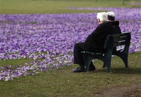 An elderly couple sit on a bench next crocus flowers in a park in Duesseldorf in this March 17, 2010 file photo. REUTERS/Ina Fassbender