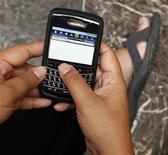 <p>Foto de archivo de una mujer navegando por internet a través de su teléfono móvil Blackberry en Yakarta, ene 10 2011. El BlackBerry, antes omnipresente en los negocios, enfrenta duros desafíos en ese mercado, porque más compañías están permitiendo que sus empleados elijan sus propios teléfonos inteligentes e incluyan aplicaciones de seguridad de otros proveedores. REUTERS/Enny Nuraheni</p>