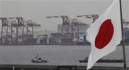 A Japanese national flag is seen in front of cargo cranes at an industrial port in Tokyo June 20, 2011. REUTERS/Kim Kyung-Hoon