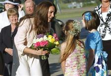 <p>Catherine, the Duchess of Cambridge, receives flowers from two girls at the airport in Charlottetown, Prince Edward Island July 3, 2011. REUTERS/Paul Darrow</p>