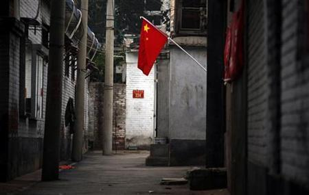 A Chinese national flag can be seen hanging down a deserted hutong, Chinese for small alley, near Beijing's Tiananmen Square July 1, 2011. REUTERS/David Gray